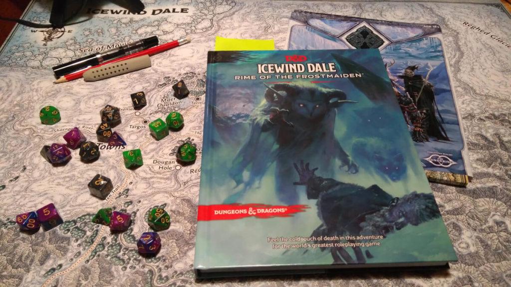 """Kampagnenbuch """"Rime of the Frostmaiden""""  und das Kampagnenheft """"Legacy of the Crystal Shard"""" auf der Posterkarte des Eiswindtals mit Würfeln und Stiften."""